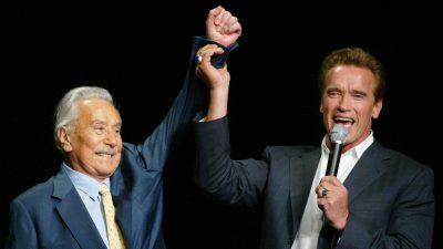 Arnold Schwarzenegger raises the arm of Joe Weider, the creator of the Mr. Olympia Bodybuilding competition, during the 39th annual Mr. Olympia event in 2003. Weider died Saturday at 93.