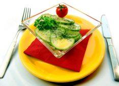 Огуречный салат на тарелке и приборы