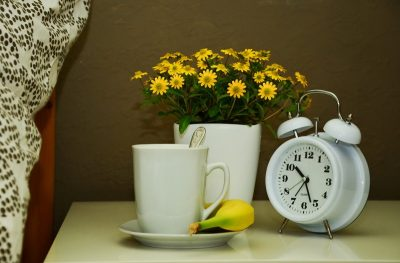 Будильник, букет и чашка на прикроватном столике