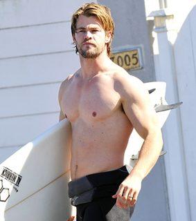 Молодой Крис Хемсворт с доской для сёрфинга