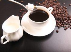 Чашка кофе, кофейные зерна, рафинад и сливки