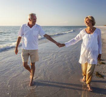 Пожилая пара гуляет по берегу моря