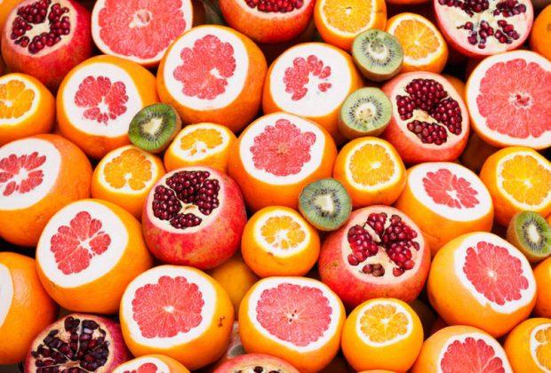 Надрезанные грейпфруты, апельсины и гранаты