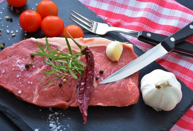 Сырое мясо, нож, помидоры и специи