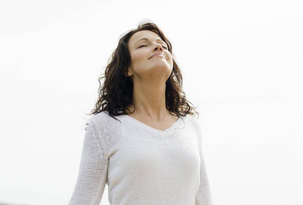 Женщина делает дыхательное упражнение