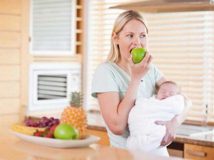 Женщина держит ребёнка на руках и ест яблоко