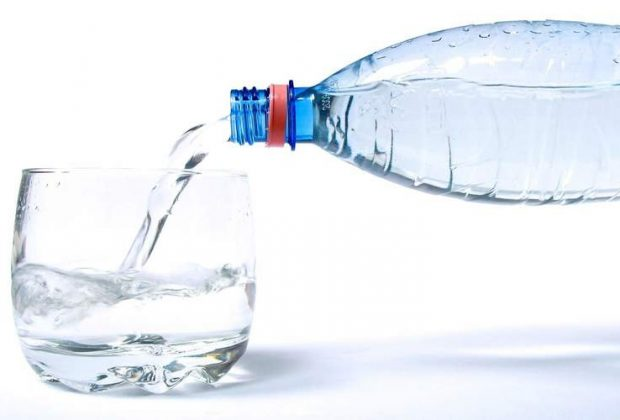 Вода из бутылки льется в стакан