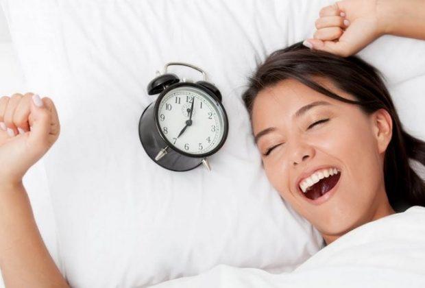 Женщина в постели с будильником