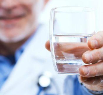 Врач протягивает стакан воды
