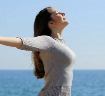Девушка у моря с раскинутыми руками