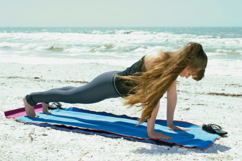 Девушка делает планку на пляже