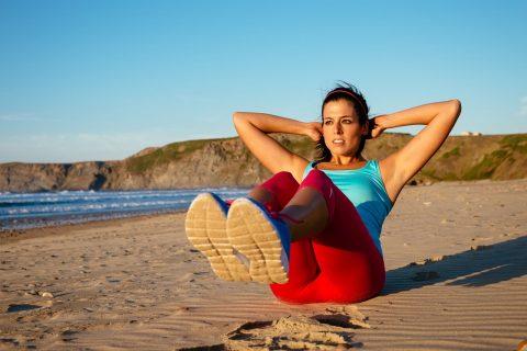 Девушка делает скручивания на пляже