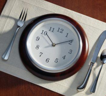 Круглые часы на салфетке и приборы