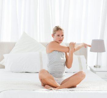 Девушка делает зарядку в кровати