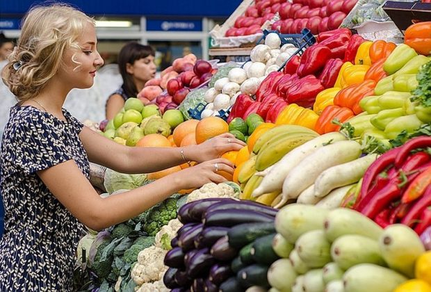 Женщина на рынке выбирает фрукты и овощи