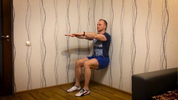 Мужчина делает упражнение «Стульчик»