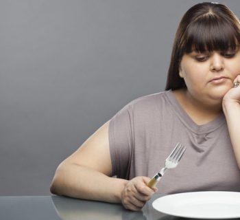 Полная девушка перед пустой тарелкой