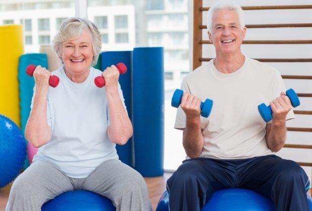 Пожилые мужчина и женщина с гантелями