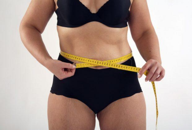 Женщина измеряет у себя талию