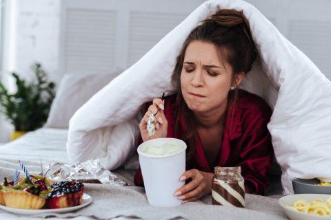Девушка сидит под одеялом и ест сладкое