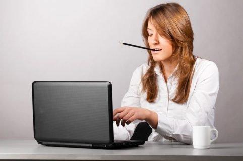 Девушка за ноутбуком с карандашом в зубах