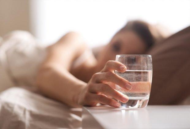 Девушка берет стакан воды