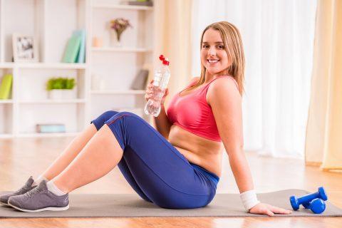 Женщина с лишним весом делает упражнения на коврике