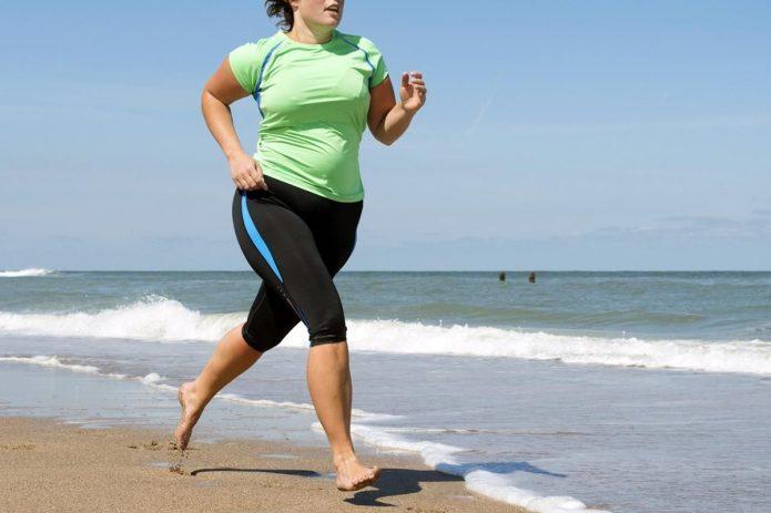 Полная женщина бежит босиком по берегу