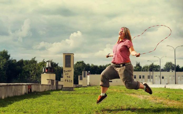 полная женщина прыгает на скакалке