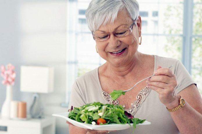 Пожилая женщина ест пирог
