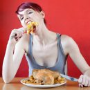 Девушка жадно ест курицу
